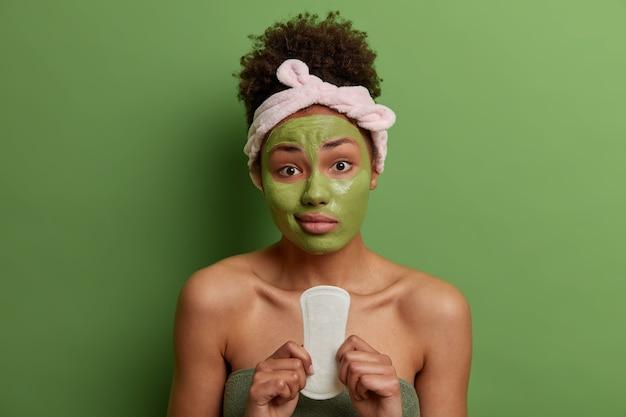 Mujer joven disgustada sostiene una toalla sanitaria para la menstruación, se aplica una mascarilla de belleza para el rejuvenecimiento, usa una diadema y una toalla, posa en el interior contra una pared verde. mujeres, belleza, concepto de higiene.