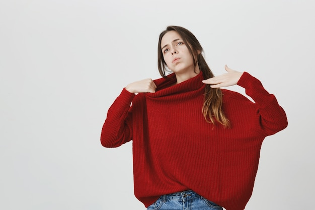Mujer joven disgustada en suéter rojo siente calor, trata de refrescarte