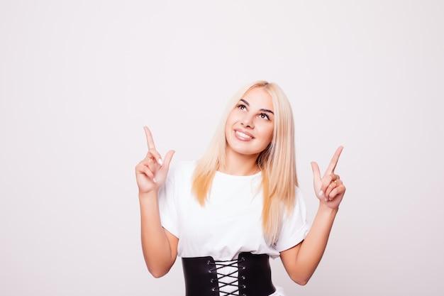 Mujer joven divertida en camisa blanca que señala el dedo hacia arriba aislado. jovencita rubia haciendo muecas y mirando hacia arriba