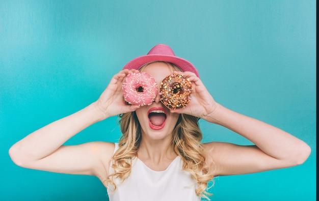 Mujer joven divertida está cubriendo sus ojos con dos donas