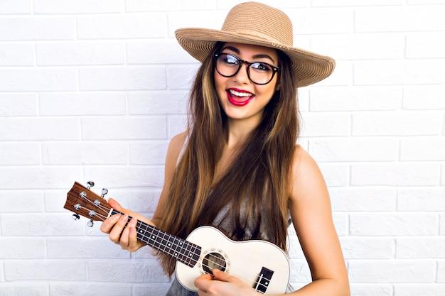 Mujer joven divertida hipster divirtiéndose y tocando en la pequeña guitarra de ukelele, cantando y bailando. con gafas vintage y sombrero de paja, alegría, estado de ánimo positivo.
