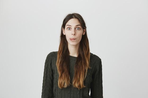 Mujer joven divertida y linda con el pelo largo, mostrando la lengua, mira algo sabroso
