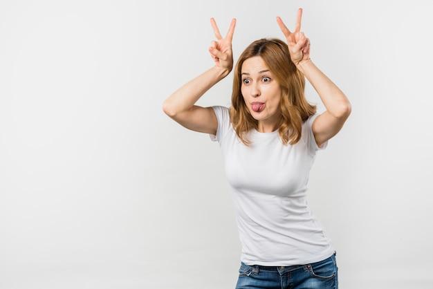 Mujer joven divertida que hace el gesto del cuerno que toma el pelo contra el contexto blanco