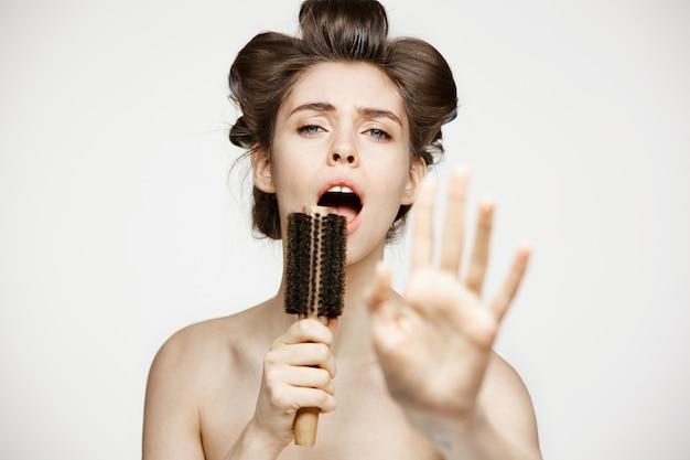 Mujer joven divertida en rizadores para el cabello y toalla regocijándose cantando en peine. belleza y spa.