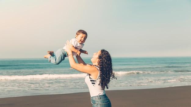 Mujer joven divirtiéndose con el bebé en la playa de verano