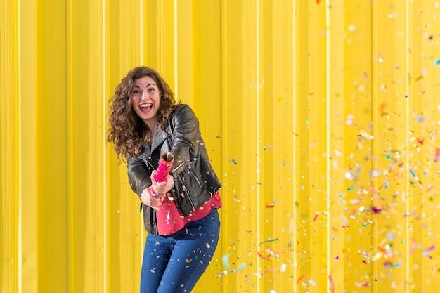 Mujer joven divirtiéndose con confeti sobre amarillo