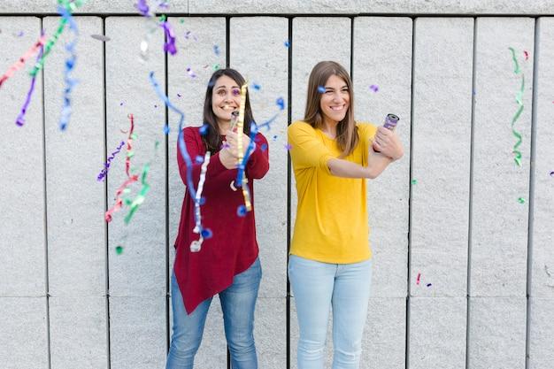 Mujer joven divirtiéndose con confeti sobre fondo amarillo