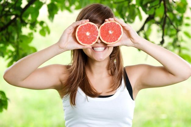 Mujer joven divirtiéndose con frutas
