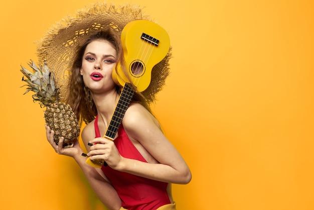 Mujer joven divirtiéndose y riendo, una fiesta de traje de baño, toca la guitarra