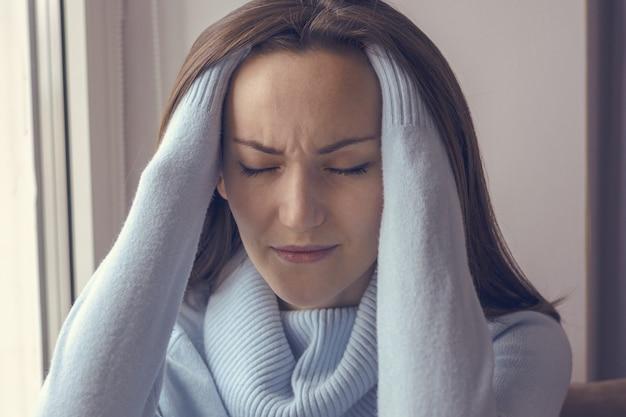 Mujer joven con dolor de cabeza en el alféizar de la ventana cerca de la ventana en casa, primer plano