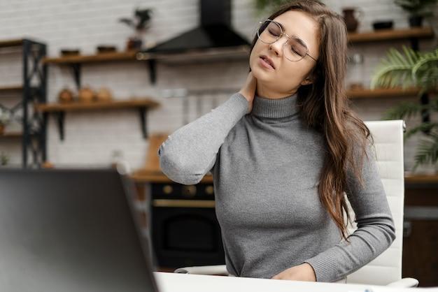 Mujer joven con dolor de cuello mientras trabaja desde casa