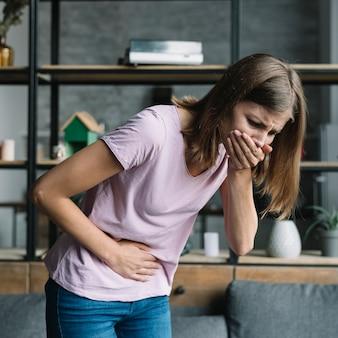 Mujer joven con dolor de estómago que sufre de náuseas.