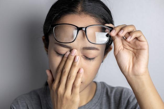 Mujer joven con dolor de ojos en un gris.