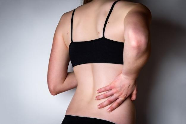 Mujer joven con dolor en los riñones.
