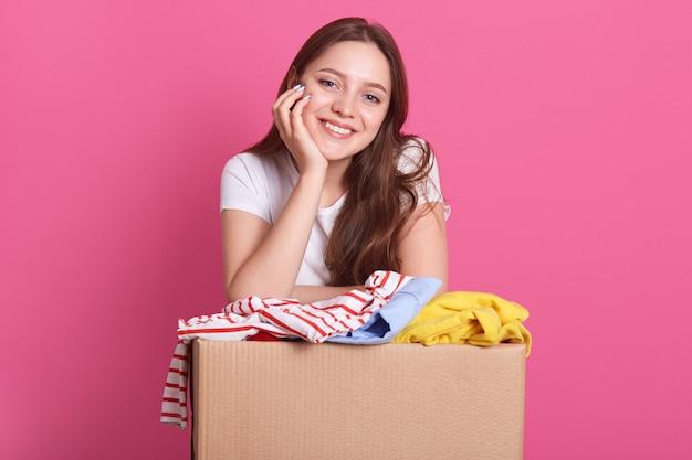 Mujer joven con donación de ropa contra la pared de color rosa, de pie con la mano debajo de la barbilla, niña mirando sonriendo directamente a la cámara, mujer con camiseta blanca. concepto de voluntariado.