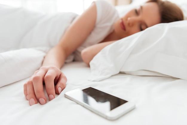 La mujer joven durmiente miente en cama cerca del teléfono.