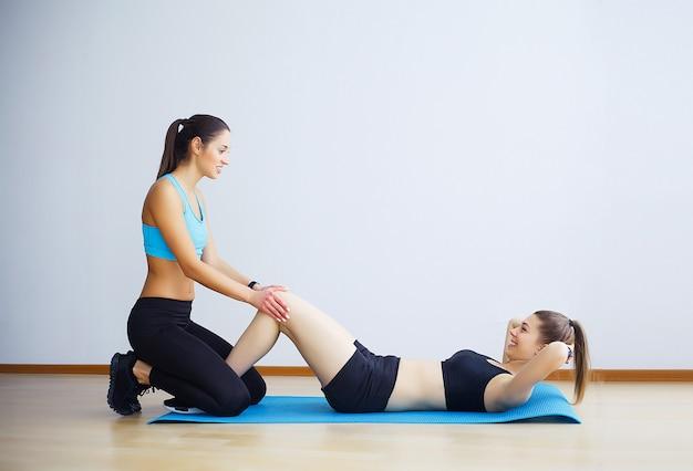 Mujer joven ejercicio de abdominales con ayuda de amiga en el gimnasio.