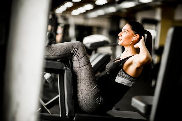 Mujer joven ejercicio abs en el gimnasio