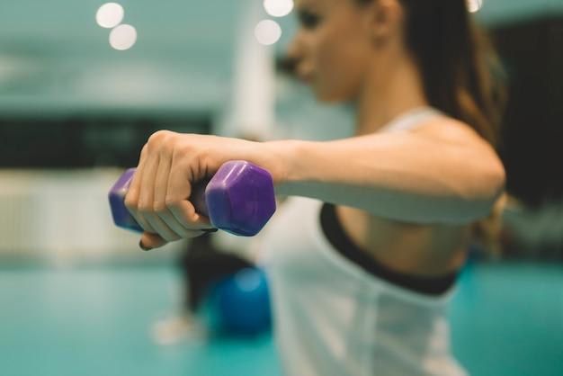 Mujer joven ejercicio con pesas en el gimnasio