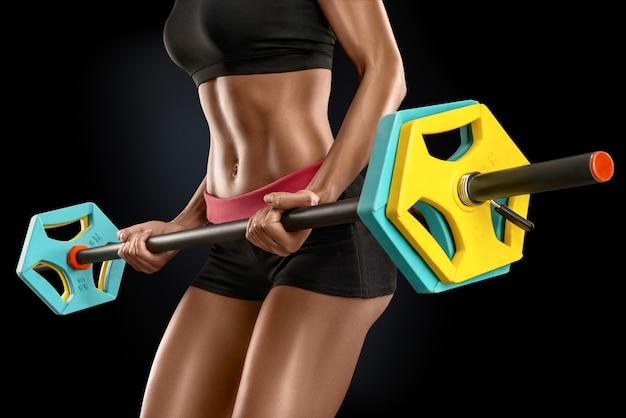 Mujer joven ejercicios con barra aislada sobre fondo negro