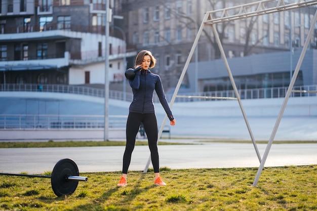 Mujer joven, ejercitar, con, un, pesas rusas, exterior, en, estadio