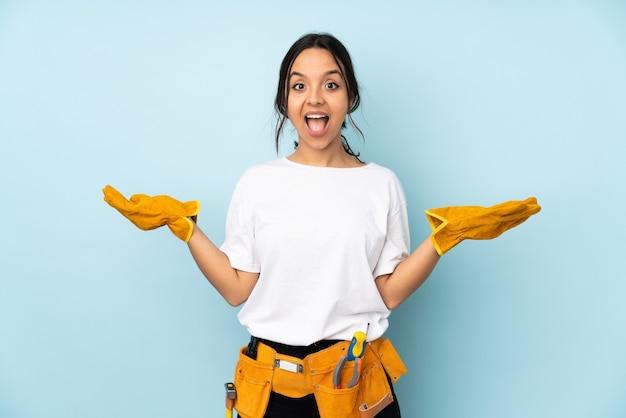Mujer joven electricista aislada con expresión facial sorprendida