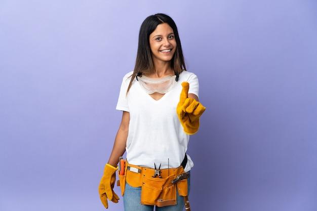Mujer joven electricista aislada en la pared púrpura mostrando y levantando un dedo