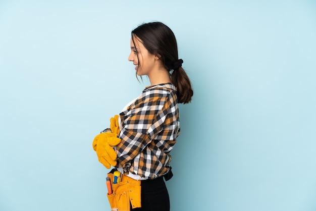 Mujer joven electricista aislada en posición lateral