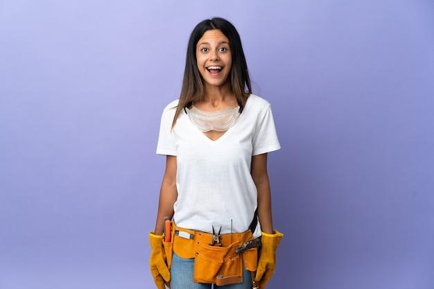 Mujer joven electricista aislada en púrpura con expresión facial sorpresa