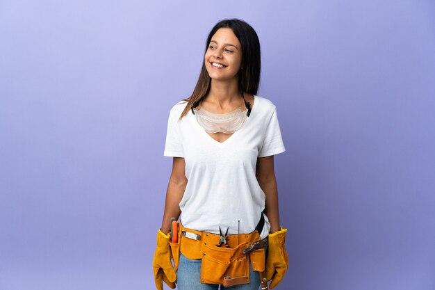 Mujer joven electricista aislada en púrpura mirando hacia un lado y sonriendo