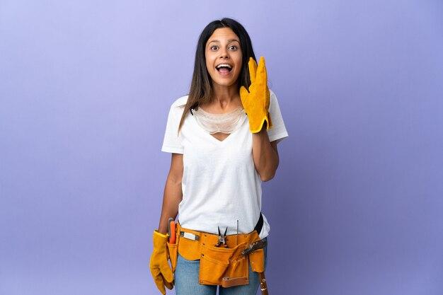 Mujer joven electricista aislada con sorpresa y expresión facial conmocionada