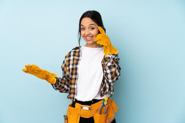 Mujer joven electricista en pared azul manteniendo una conversación con el teléfono móvil con alguien