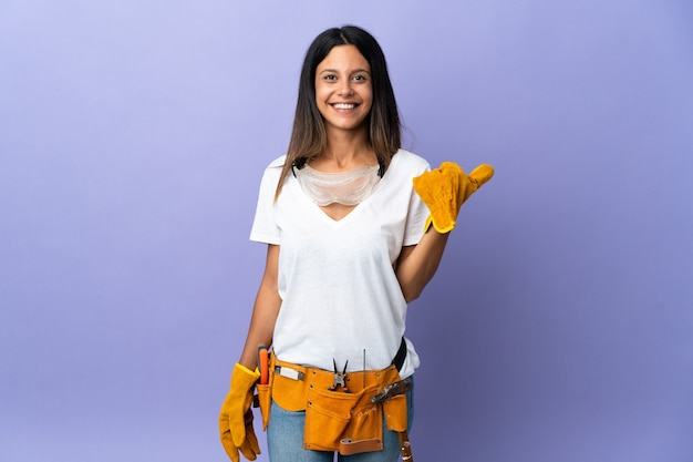 Mujer joven electricista sobre pared aislada