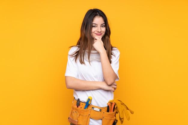 Mujer joven electricista sobre pared amarilla riendo