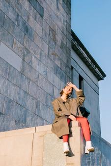 Mujer joven elegante agotada que se sienta en la pared