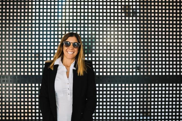 La mujer joven elegante alegre con las gafas de sol acerca a la cerca
