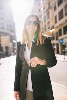 Mujer joven elegante alegre con las gafas de sol en la calle