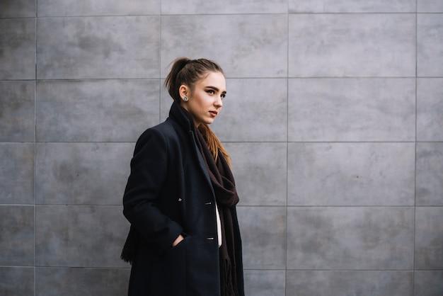 Mujer joven elegante en capa con la bufanda cerca de la pared gris