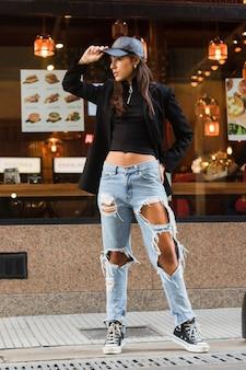 Mujer joven elegante en el casquillo negro que se coloca delante de restaurante