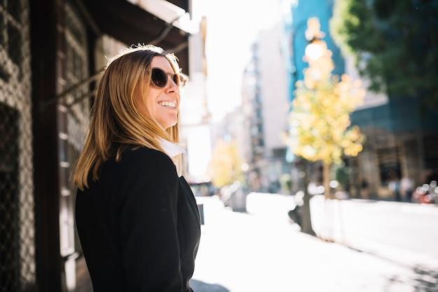 Mujer joven elegante feliz con las gafas de sol en ciudad en día soleado