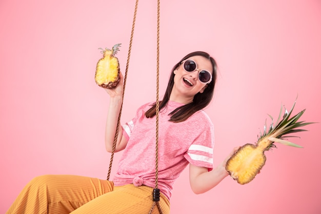 Una mujer joven y elegante en un look de verano monta en columpio en rosa aislado.