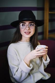 Mujer joven elegante positiva en sombrero y lentes con la taza de bebida