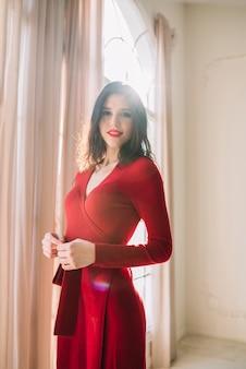 Mujer joven elegante positiva en vestido rojo cerca de la ventana en sitio ligero