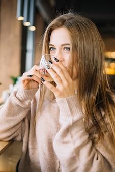 Mujer joven elegante que bebe de la taza en café