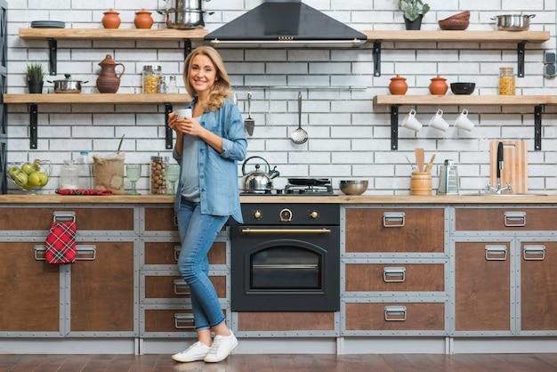 Mujer joven elegante que se coloca en la cocina modular que sostiene la taza de café disponible