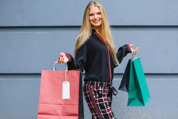 Mujer joven elegante que se coloca delante de la pared que sostiene bolsos de compras coloridos en manos