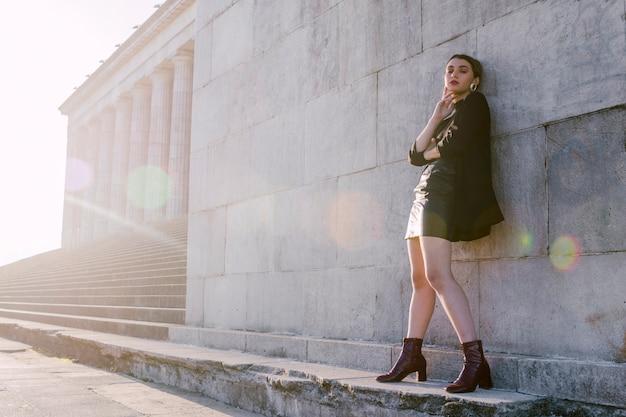 Mujer joven elegante que se coloca en pared con luz del sol