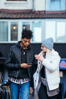 Mujer joven elegante que habla con su novio hermoso que usa el teléfono móvil