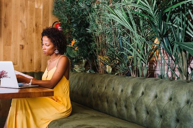 Mujer joven elegante que mira documentos con el ordenador portátil en la tabla de madera en el restaurante