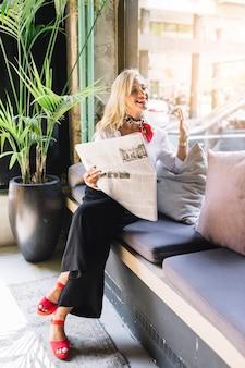 Mujer joven elegante que se sienta en el restaurante que lleva a cabo el periódico que hace gesto